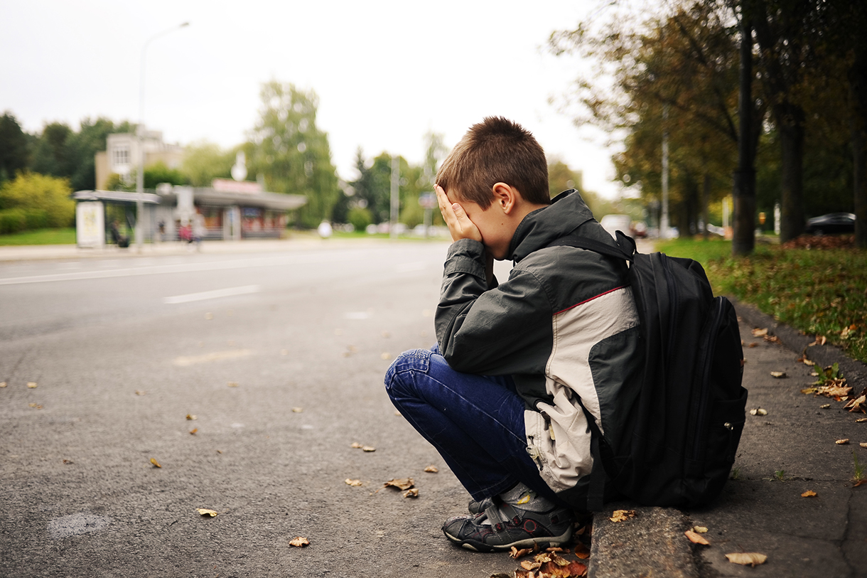 Boy sat on a curb with his head in his hands