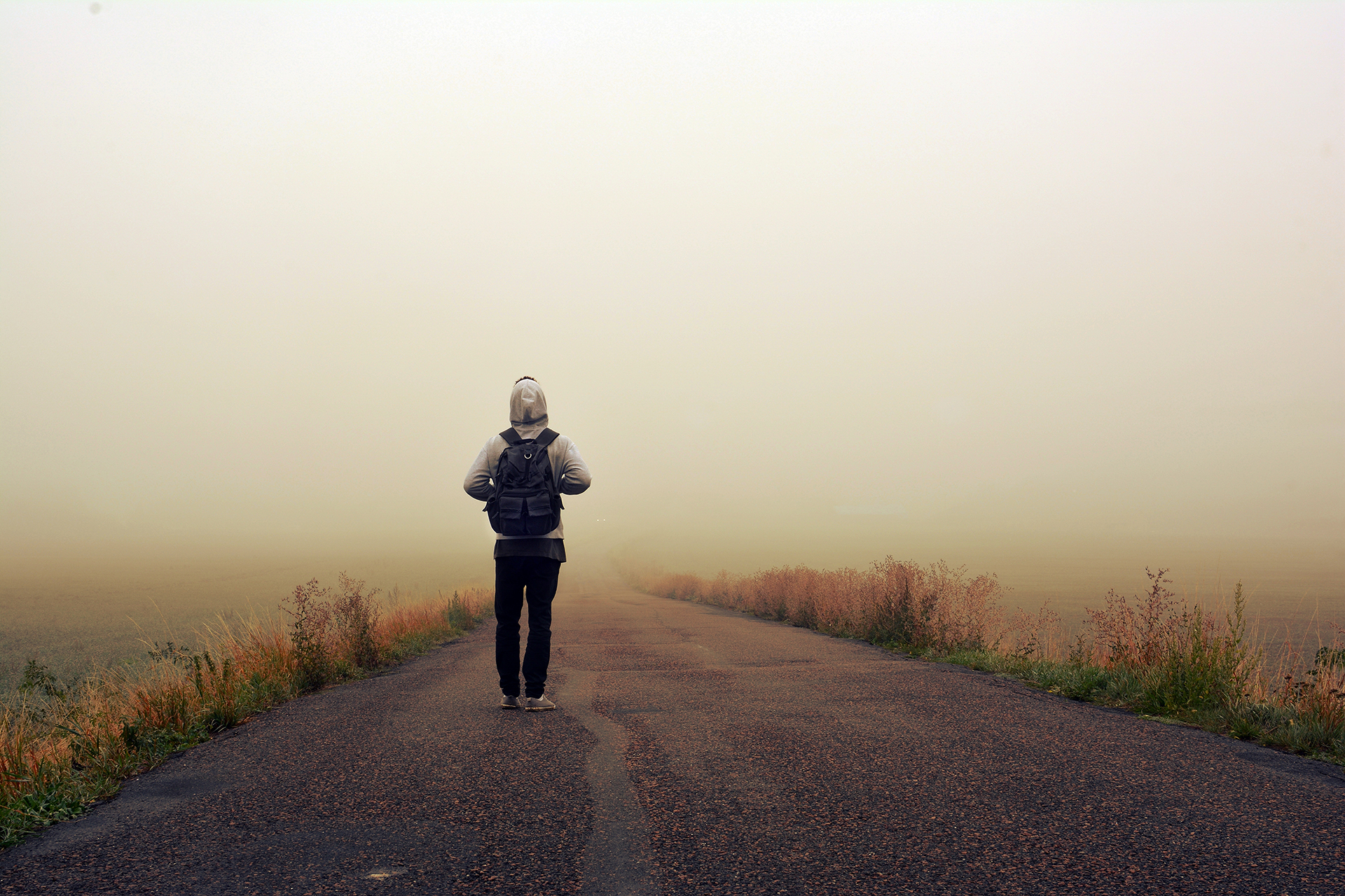 Someone stood on isolated lane facing away from the camera looking at the road
