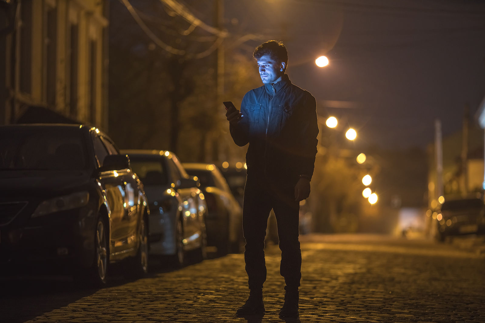 Male alone on a dark street looking at his phone
