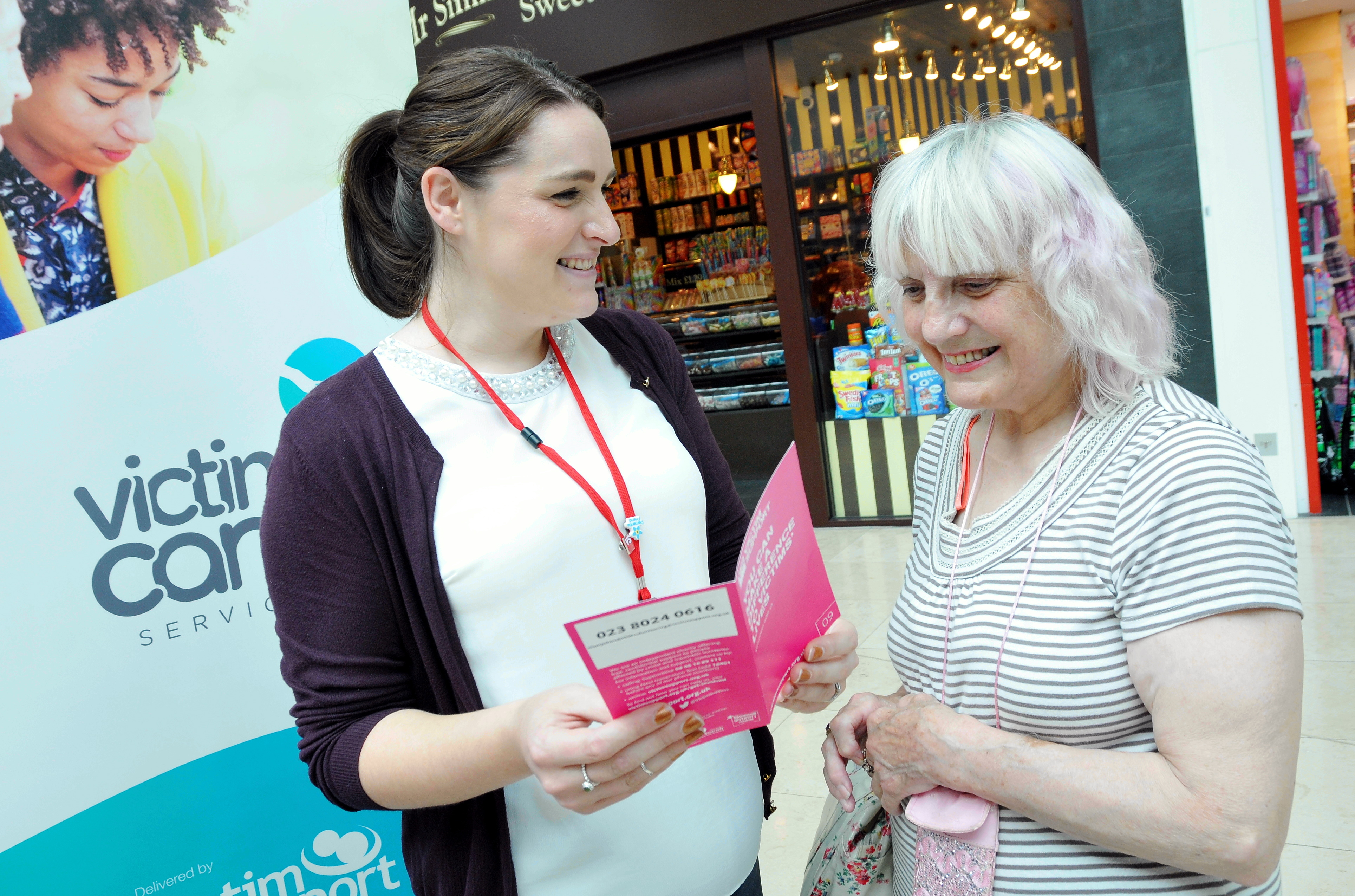 Victim Care Service Employee holding a leaflet talking to a member of the public during the event